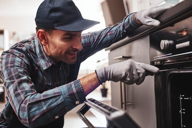 Não demore para reparar o close up do reparador examinando o forno