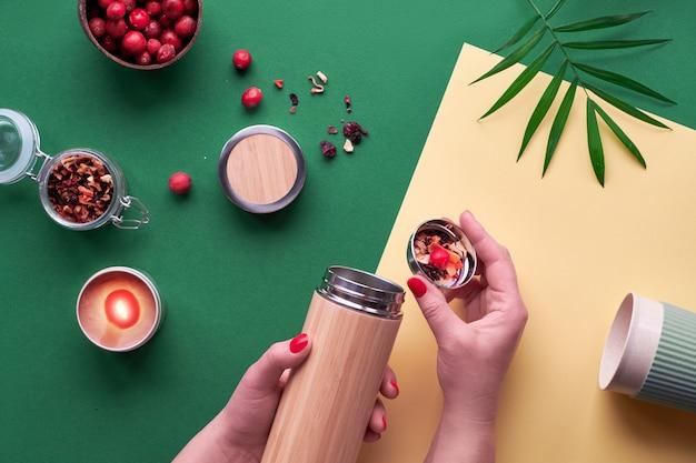 Não desperdice chá, fazendo infusão de ervas em um frasco de aço de bambu com isolamento ecológico com mistura de ervas e amora fresca. na moda plana criativa leiga, vista superior em papel amarelo verde de dois tons.
