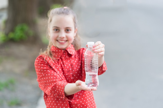 Não espere, hidrate. garrafa de foco seletivo de água potável. menina bebendo água para matar a sede. criança com sede. sede ou desidratação. extinguindo a sede. conceito de sede.