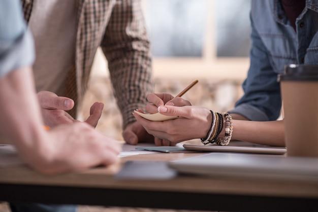 Não esquecer. bela jovem positiva em pé com seu colega e fazendo anotações enquanto trabalhava com ele