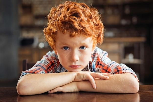 Não estou com humor hoje. retrato de um menino ruivo mal-humorado, encostado em uma mesa de jantar e olhando para a câmera com os olhos cheios de tristeza em casa.