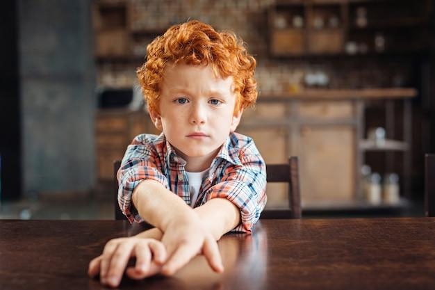 Não estou com um humor brincalhão hoje. criança de cabelo encaracolado temperamental sentado a uma mesa de madeira e esticando as mãos enquanto olha para a câmera com os olhos cheios de tristeza.
