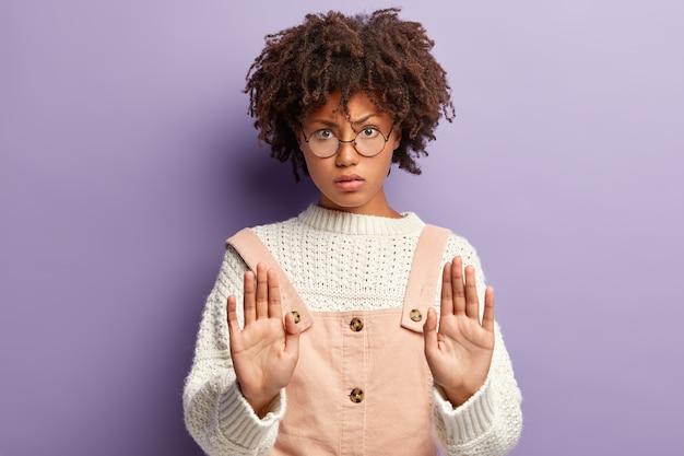 Não, eu recuso, não é interessante. mulher afro-americana séria mantém paralisia durante o gesto de parada ou rejeição