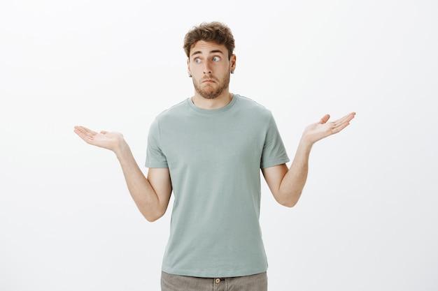 Não faço ideia de como isso aconteceu. retrato de um cara engraçado desajeitado e desavisado de camiseta e brincos, fazendo uma expressão sem noção e encolhendo os ombros com as palmas das mãos abertas