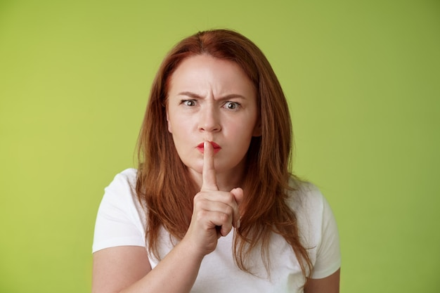 Não falar durante o exame estrito sério olhando descontente mulher ruiva de meia-idade franzindo a testa desapontada silenciando diga cale dedo indicador lábios pressionados mantenha silêncio gesto parede verde