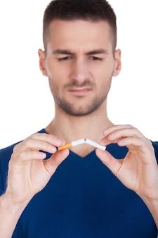 Não fumar mais. jovem sério segurando uma tesoura perto do cigarro em pé, isolado no fundo branco