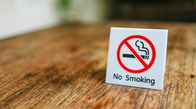 Não fume sinal. rótulo de não fumar no público. placa de proibição de fumar na mesa de madeira do hotel
