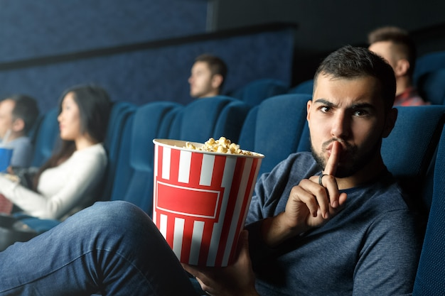 Não há conversa aqui. homem bonito, fazendo o gesto de silêncio para a câmera enquanto está sentado na sala de cinema