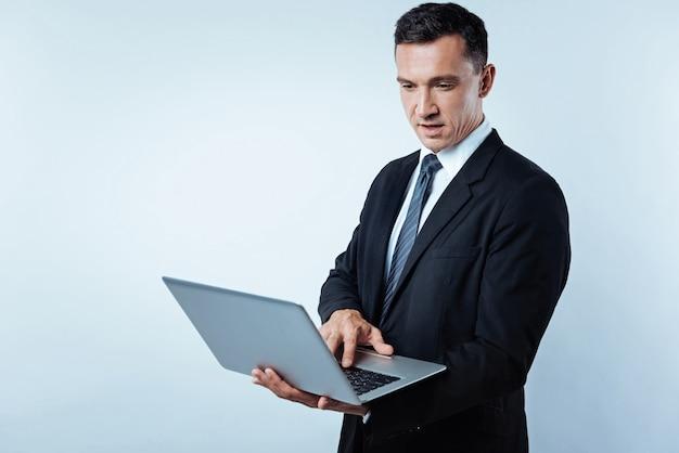 Não há mais tempo para relaxar. cintura para cima foto de um empresário confiante focalizando sua atenção em uma tela de um computador em sua mão enquanto lê uma carta comercial sobre o fundo.