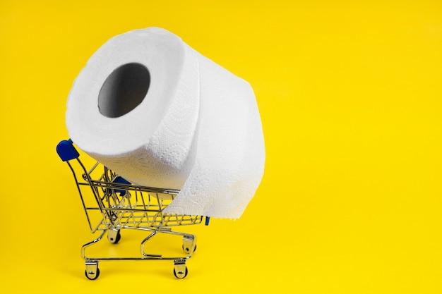Não há papel higiênico carrinho de compras para produtos com papel higiênico em um fundo amarelo
