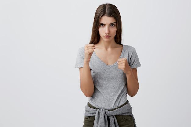 Não mexa comigo, garoto. garota jovem atraente morena estudante caucasiano confiante com cabelos longos, elegante roupa casual, segurando os punhos na frente dela com expressão irritada e média.