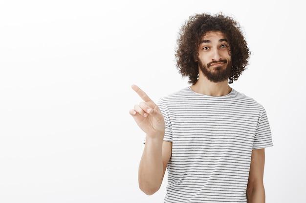 Não, não pense nisso. irmão adulto bonito e confiante com cabelo e barba cacheados, sorrindo e erguendo uma sobrancelha enquanto rejeita a oferta