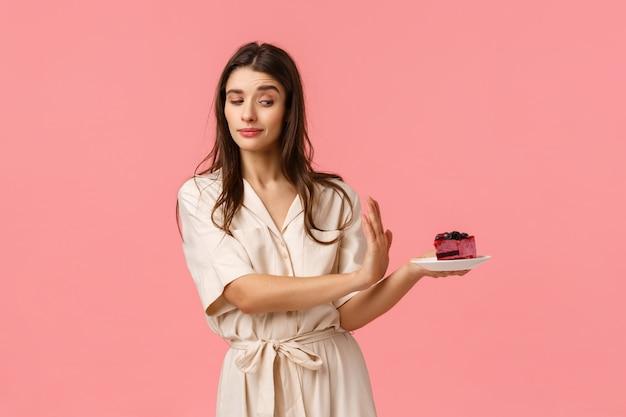 Não, obrigado. garota com vontade forte, rejeitar o pedaço de bolo, segurando o prato e fazendo parar