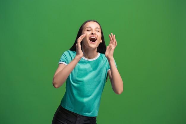 Não perca. jovem mulher casual gritando. gritar. mulher chorando emocional, gritando sobre fundo verde do estúdio. retrato feminino de meio corpo. emoções humanas, conceito de expressão facial. cores da moda