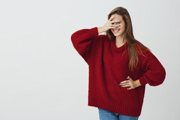 Não posso cumprir minha promessa e não olhar. foto de estúdio da encantadora jovem brincalhão na camisola solta vermelha, cobrindo os olhos com a mão, mas espreitando por entre os dedos, querendo ver a surpresa
