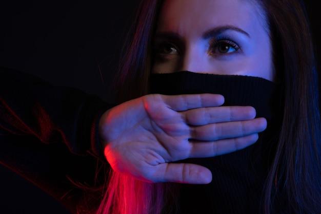 Não posso dizer nada. garota fecha a boca com as palmas das mãos cruzadas em neon.