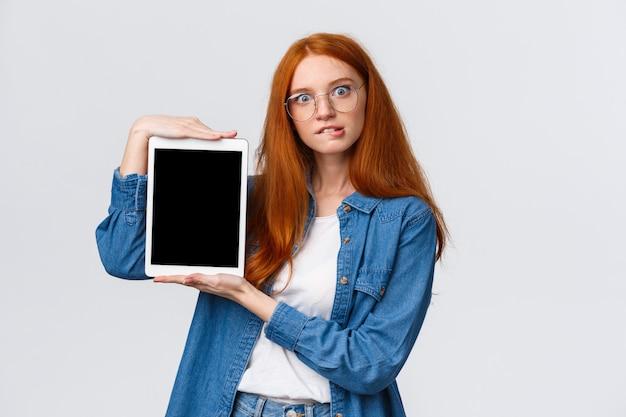Não posso resistir à tentação, adicione ao carrinho agora. mulher ruiva animada tentadora e curiosa de óculos, desejo de morder o lábio, comprar algo on-line, mostrando a tela do tablet digital, branca