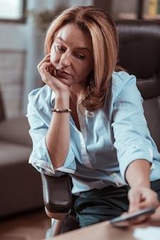 Não recebendo ligação. mulher loira atraente e elegante se sentindo triste por não receber uma ligação do marido