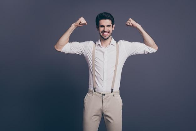 Não se esqueça do treinamento de ginástica. retrato de homem de negócios machista levantar dois grandes bíceps vestidos formalwear camisa branca calça suspensórios bege.