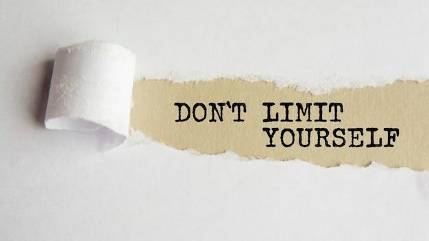 Não se limite. palavras. texto em papel cinza em fundo de papel rasgado