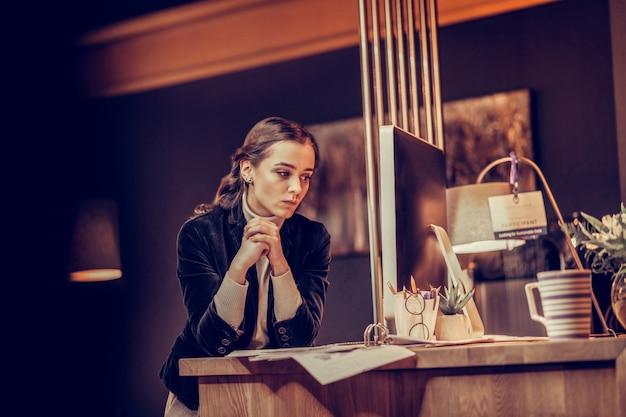 Não se preocupe. mulher de cabelos compridos atenta apoiando os cotovelos na mesa enquanto está perdida em pensamentos