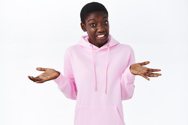 Não sei. garota afro-americana confusa encolhendo os ombros com as mãos abertas para o lado, fazendo um sorriso constrangido e desajeitado