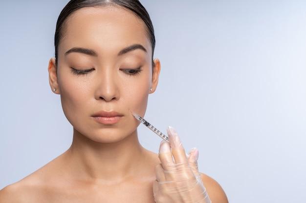 Não tenha medo. jovem visitando cosmetologista, aplicando injeção de beleza