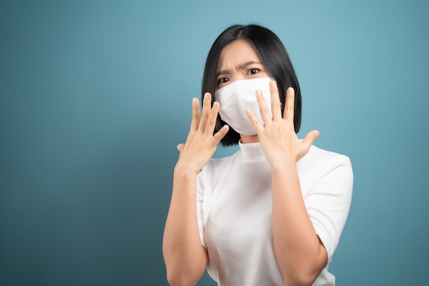 Não toque em seu rosto. mulher asiática usando máscara de higiene, mostrando sinal de parada de mão e em pé