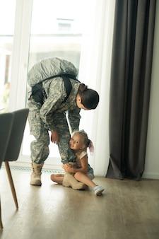 Não vá. filha emocionalmente amorosa que não deixa ir a mãe servindo nas forças armadas