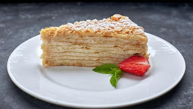 Napoleão de pedaço de bolo, em um prato branco, contra um fundo escuro