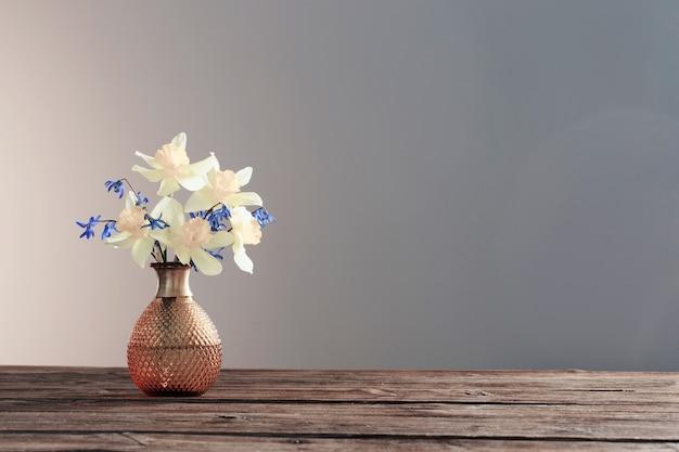 Narciso amarelo e snowdrops azuis em um vaso na mesa de madeira em fundo escuro