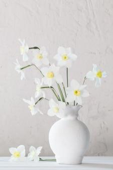 Narciso branco em um vaso na mesa de madeira
