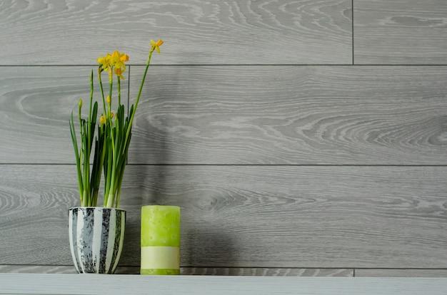 Narciso em um vaso de flores e uma vela verde em um fundo de parede de madeira. espaço para texto.