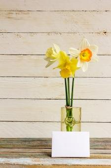 Narcisos amarelos amarelos e brancos da flor de três molas com alianças de casamento douradas no vaso de vidro com cumprimento do cartão em branco em um de madeira branco.