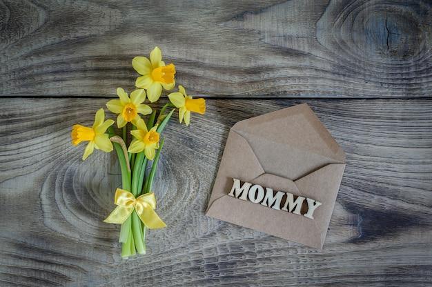 Narcisos com envelope. cartão de felicitações feliz dia das mães.