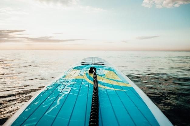 Nariz de stand up paddle board flutuando em um belo lago
