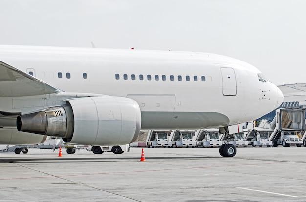 Nariz e cabina do piloto, no rack frontal do close-up do chassi, contra o fundo da escada e da máquina do aeroporto.