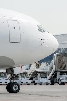 Nariz e cabine, no rack frontal do close-up do chassi, contra o fundo da escada e da máquina do aeroporto.