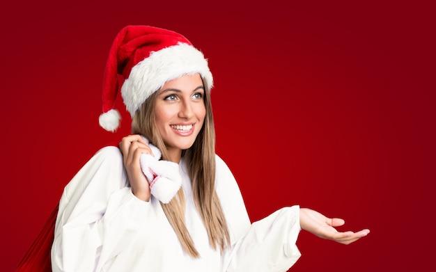 Nas férias de natal jovem mulher loira pegando um saco cheio de presentes ao longo da parede vermelha isolada