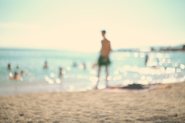 Nas férias de verão. silhueta de um homem jogando tênis na praia.