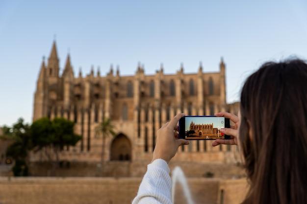 Nas férias, jovem de pele clara tirando uma foto da catedral de palma de maiorca com seu telefone.