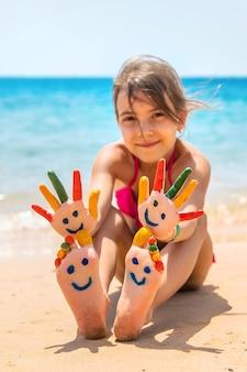Nas mãos da criança, um sorriso com tintas no mar