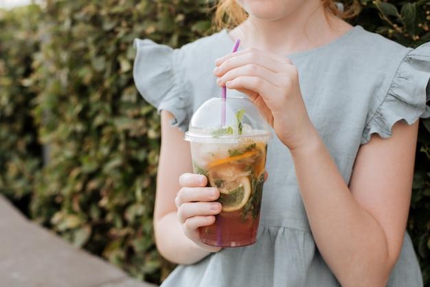 Nas mãos das crianças, um copo de plástico com limonada gelada.