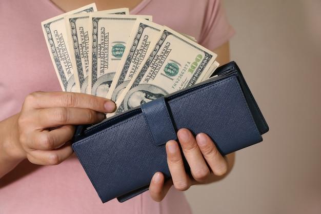 Nas mãos das mulheres é a carteira de couro bule com um maço de cem dólares.