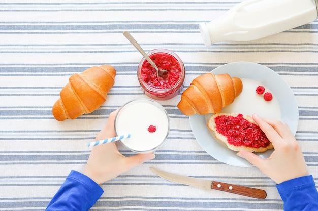 Nas mãos de garotas o copo com leite e sanduíche com geléia. há croissants, geléia, uma garrafa de leite, uma faca sobre uma toalha de linho. produtos agrícolas orgânicos saudáveis para café da manhã ou almoço.