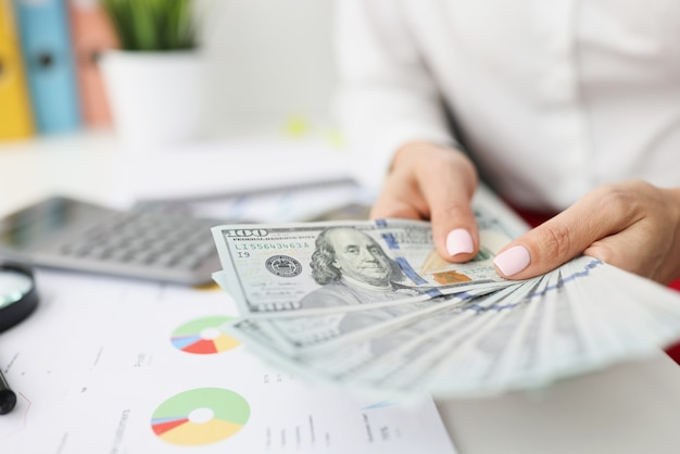 Nas mãos de mulheres, notas de cem dólares na mesa são números comerciais e financeiros em gráficos