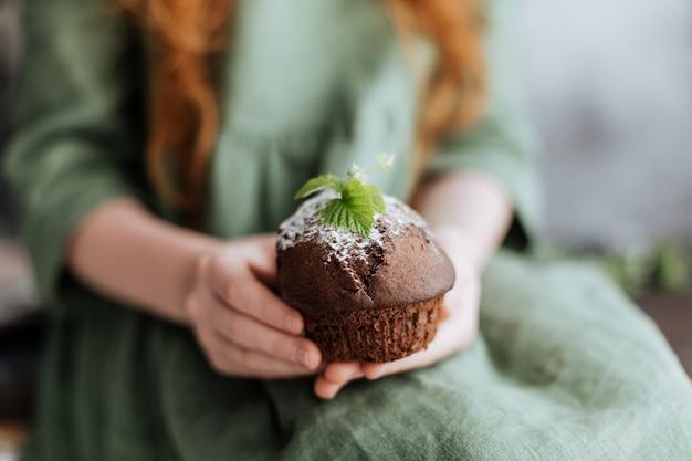Nas mãos de um bolinho de chocolate decorado com uma folha verde.
