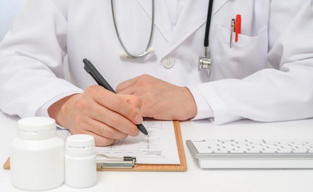 Nas mãos de um médico que escreve um prontuário médico.