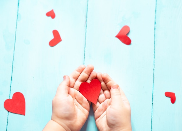 Nas mãos de uma criança segurando um coração vermelho sobre um fundo azul