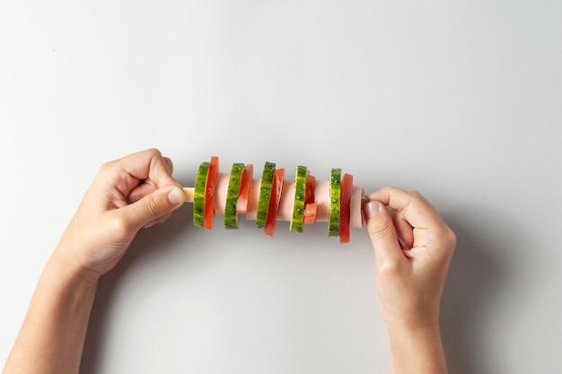 Nas mãos de uma criança, um sanduíche incomum em uma espada. tem uma linguiça, um pepino, um tomate